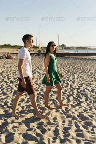Couple walking on sand against clear sky