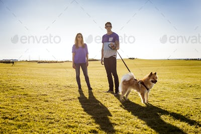 Full length of couple with dog standing at park on sunny day