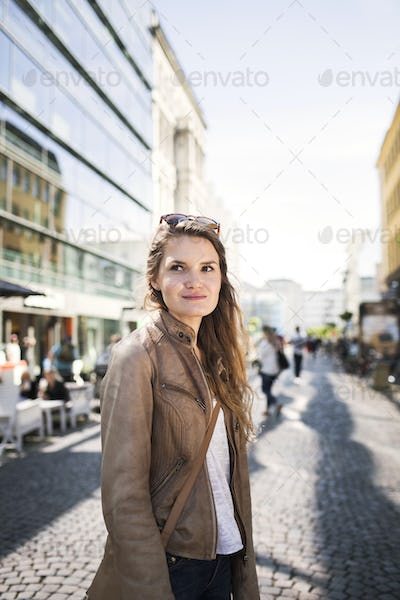 Beautiful young woman on city street