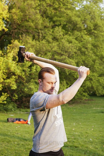 Young man lifting hammer in park