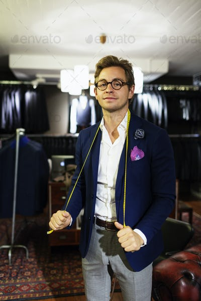 Portrait of handsome designer holding tape measure around neck in showroom