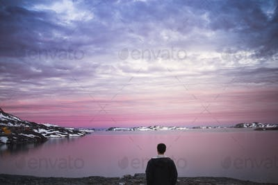 Rear view of young man on shore enjoying the sunset view during winter