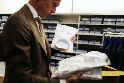 Side view of salesman analyzing shirts in clothing store