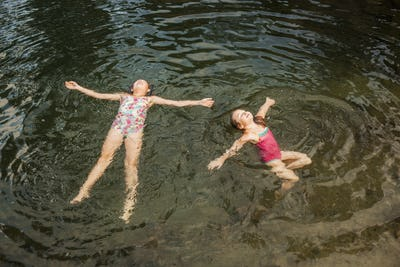High angle view of sisters floating in rippled lake
