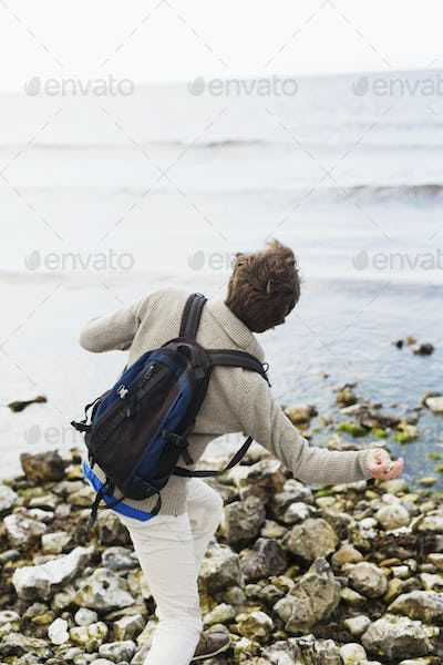 Rear view of man throwing stones in water at beach