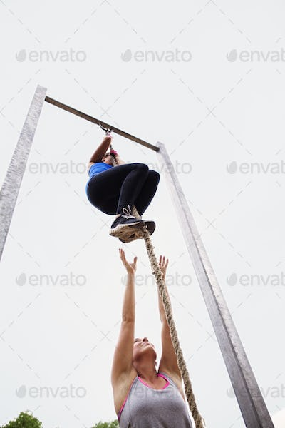 Low angle view of woman motivating friend climbing rope against clear sky