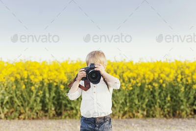 Boy photographing through SLR camera on rapeseed field against sky