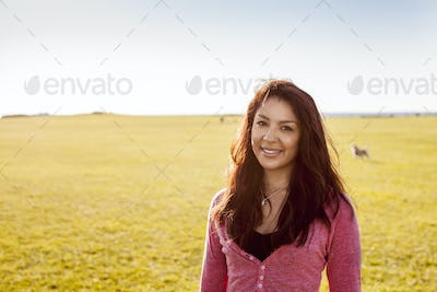 Portrait of smiling woman at park on sunny day