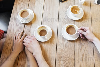 High angle view of couple holding hands while having coffee in restaurant
