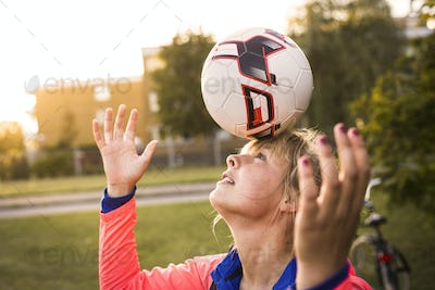 Sporty woman balancing soccer ball on forehead at park