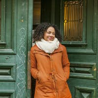 Smiling young woman in winter coat standing at the entrance of cafe