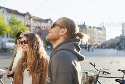 Happy couple looking away while standing on city street