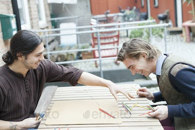 Happy male friends playing Mikado at cafe backyard