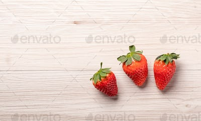Three strawberries on wood background