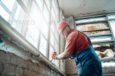 Builder on a construction site working on a windowsill with a hammer