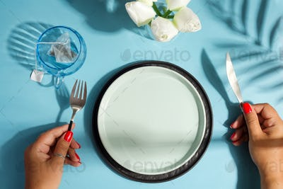 Dinner table with ceramic plate and woman hand holding knife and fork