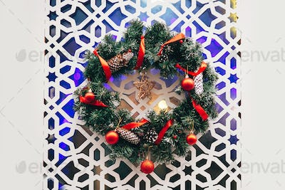 Traditional christmas wreath with red baubles ornaments and pine cones on modern white door