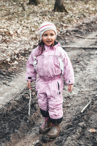 Concept - happy childhood. Little girl plays in swamp, children's fun, dirty and wet shoes