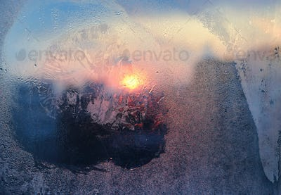 Ice pattern and water drops on glass on a sunny winter morning