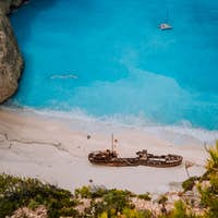 Shipwreck on Navagio beach. Azure turquoise sea water and paradise sandy beach in evening light