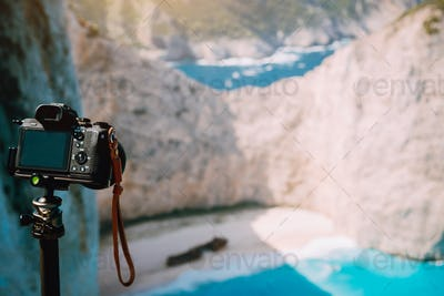 Digital camera on tripod capture photo of Shipwreck in Navagio beach in morning sun light. Famous
