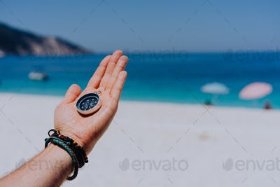 Stretched hand palm with black metal compass against sandy beach and blue sea. Follow your way, goal