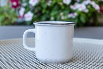 Placeit - Coffee cup mockup on a table, blur green background.