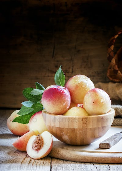Fresh white nectarines in a wooden bowl