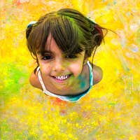 Laughing girl with paint stained her face.