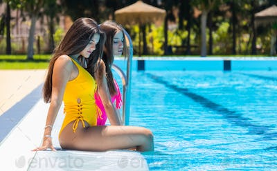Two teenagers girls at swimming pool