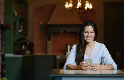 Smiling woman sitting and table and using smartphone