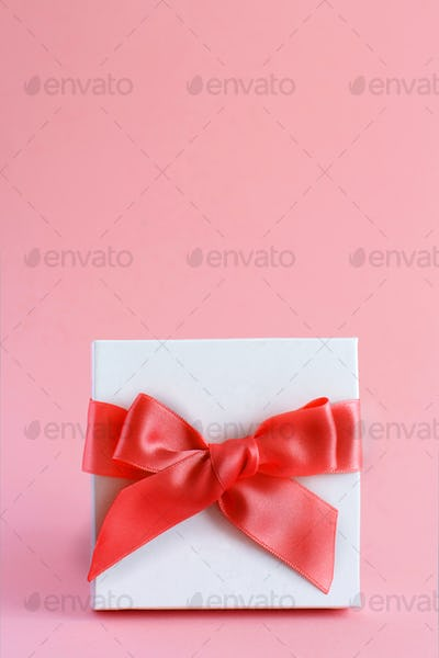 White gift box with a bow on a light pink background