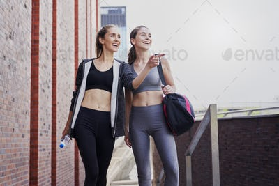 Two smiling athletic women in sports clothes pointing their finger