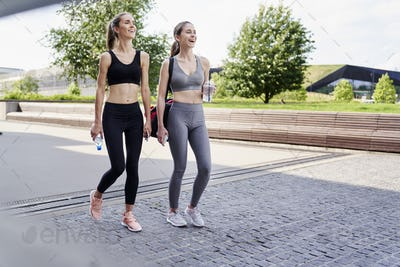 Two athletic smiling women going to training