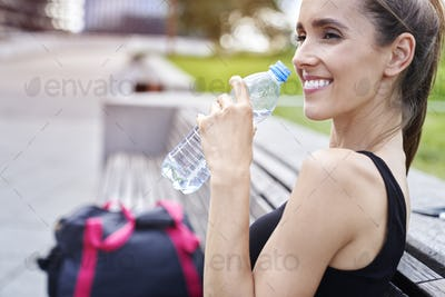 Happy athletic woman drinking water after training