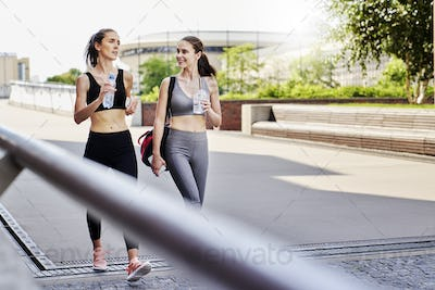 Two athletic women talking on the way to training