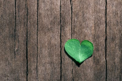 Heart-shaped part of shamrock leaf on shabby wooden background.