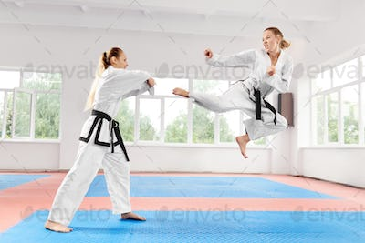 Two young women wearing in kimono and black belt training karate martial arts