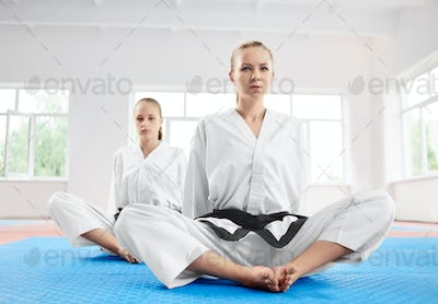 Two young karate girl sittting in lotus position after training in light gym