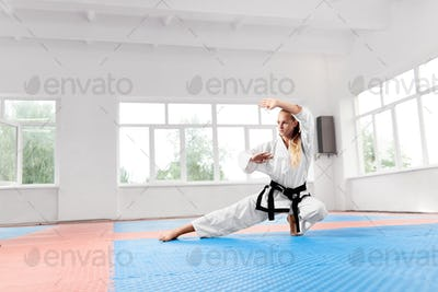 Strong girl wearing in white kimono with black belt practicing karate