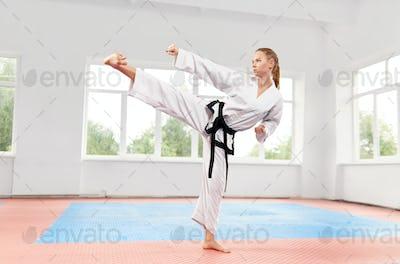 Woman performing martial arts high kick at fight class