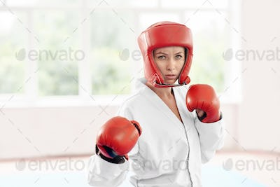 Professional female karate fighter standing in position against big window