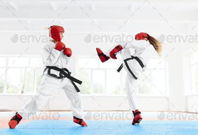 Two female fighter practicing karate kick and punch
