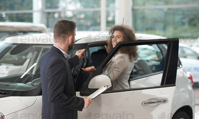 Happy woman taking keys oh new car from manager