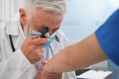 Doctor diagnosing disease of skin on patient's hand