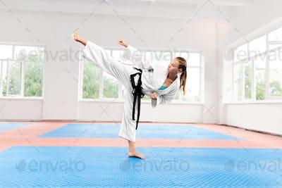 Sporty karate woman against big window standing in karate position
