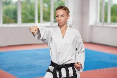 Girl wearing in white kimono with black belt standing in karate pose