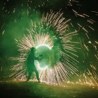 Fire dancers swing, spinning green fire and man juggling with bright sparks in the night
