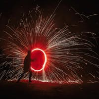 Fire dancers swing, spinning red fire and man juggling with bright sparks