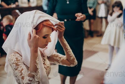 Stylish bride praying during matrimony wedding ceremony in church